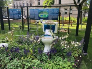 Art installation of a toilet with flowers on it in public garden